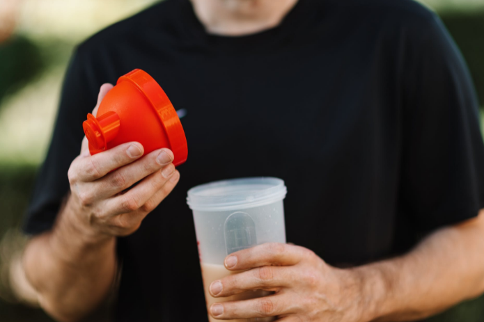man holding protein shaker